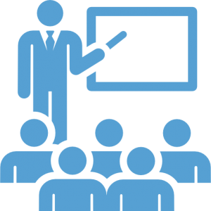 This is a Carolina Blue icon showing a teacher teaching at a blackboard in front of a class.